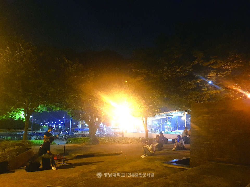 A YU student and citizen are busking at the Poles Garden.(Photo by reporter Kang Sin-hyung)